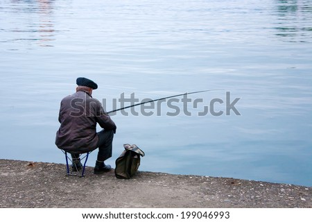 Old fisherman sitting on a wharf - stock photo