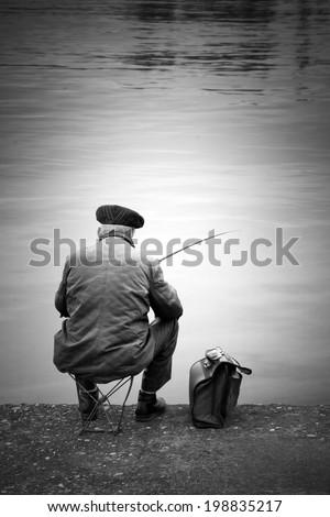 Old fisherman sitting on a wharf, monochrome - stock photo