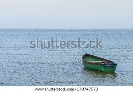 Old fishing boat anchored at a beach of the Baltic Sea - stock photo