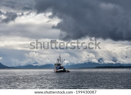 Old fishing boat in Southeast Alaska with stormy skies. - stock photo
