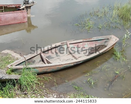 Old fishing boat in the river. - stock photo