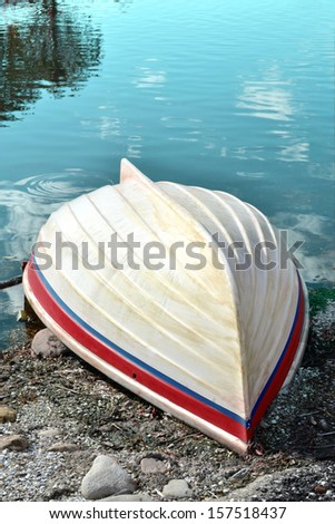 old fishing boat on rocky shore - stock photo