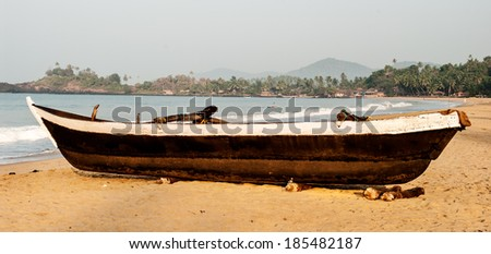 Old fishing boat on the sandy shore. In Goa - stock photo