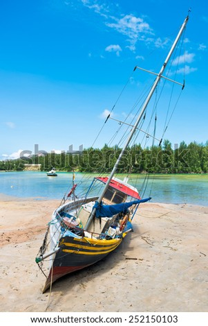 Old fishing boat on Tropical beach at Praslin island Seychelles. Vertical shot - stock photo