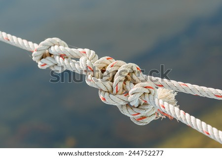 Old fishing boat rope with a Tied Knot on gray background - stock photo