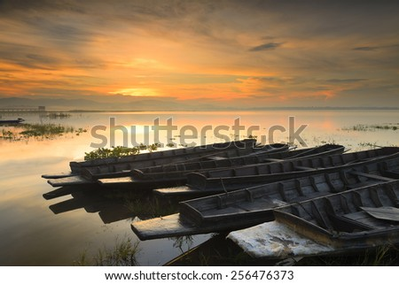 Old fishing boats at sunrise Bang Phra reservoir Thailand - stock photo