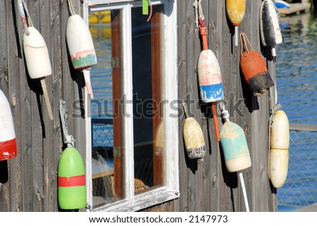 old fishing floats on building - stock photo