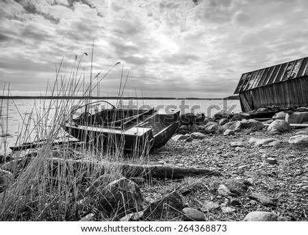 Old fishing motor boat and barn on lake coast in Karelia. Black and white photo - stock photo