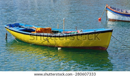 Old fishing rowing boat painted in yellow on the water on a sunny summer day - stock photo