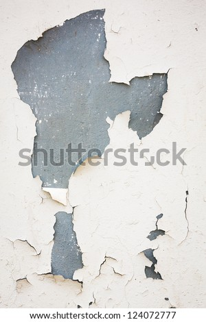 Old flaky white paint peeling off of a wall - stock photo