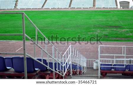 Old football stadium with blue tribunes. Shallow DOF - stock photo