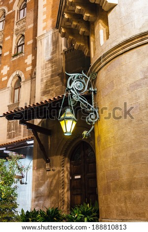 Old forged lantern at night on the background wall with bas relief in Istanbul, Turkey - stock photo