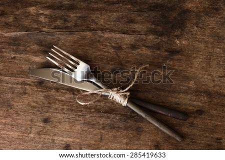 old fork and knife tied with a rope - stock photo