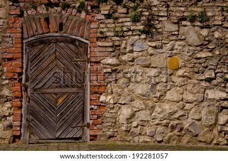 Old fortress door in the brick wall - stock photo