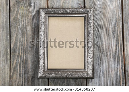 Old frame with empty canvas on wooden background - stock photo