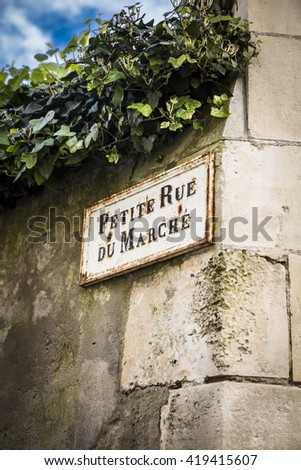 Old French street sign Petite Rue Du Marche or Market alley on an old limestone wall, Ile de Re, France - stock photo