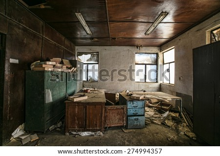 Old furniture and books in abandoned factory building  - stock photo