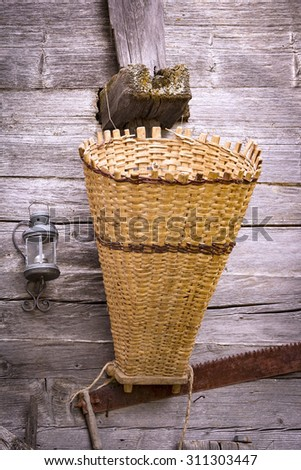 Old garden tools (basket and saw blade) are hanging on wooden timbers. - stock photo