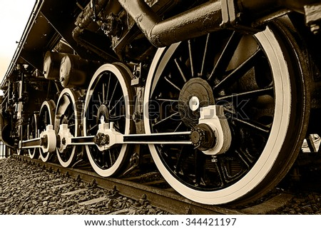 Old german steam locomotive, built in 1940, in a museum. The heaviest locomotive, 85 tons, that circulated in Romania during the Second World War. Detail and close up of huge wheels. Sepia processing. - stock photo