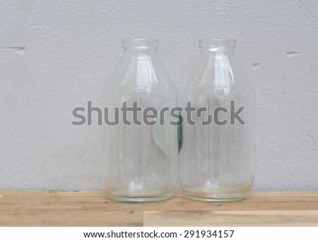 Old glass bottles on wooden shelf. - stock photo