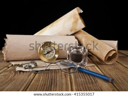 old glasses, paper, pen, clock and compass on black background - stock photo