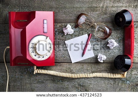 Old glasses with sheet for notes, pencil and red vintage phone on wooden background   close-up, top view, pick up the phone - stock photo