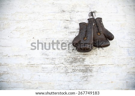 old gloves hanging on a brick wall - stock photo