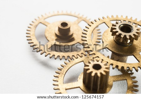 old gold clock gear on white background - stock photo
