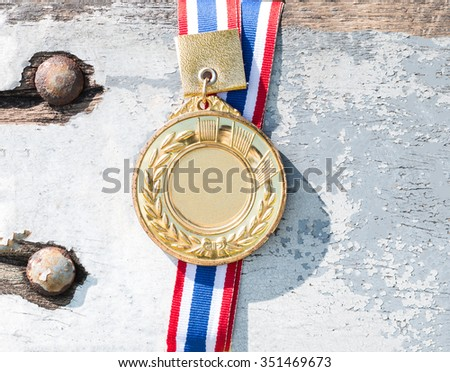old gold medal on old wood and Metal plates background, blank face for text : concept to the winner - stock photo