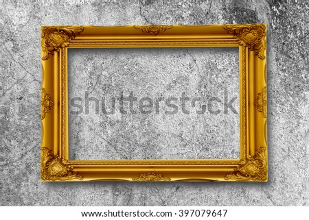 Old gold picture frame on grunge wall. - stock photo