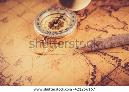 Old  gold vintage compass and pencil on vintage map - stock photo