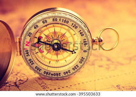 Old  gold vintage compass on vintage map - stock photo