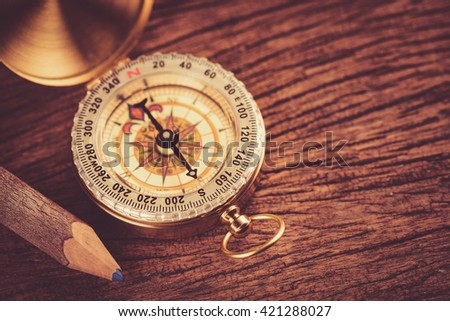 Old  gold vintage compass with pencil on wood background - stock photo