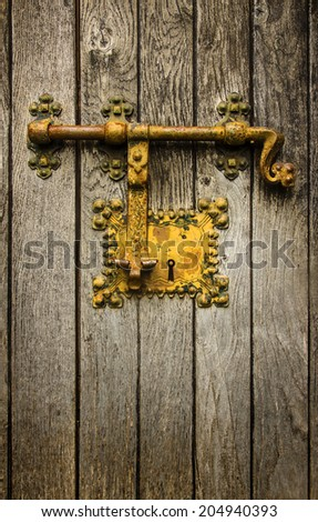 Old golden latch on a wooden door - stock photo