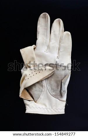 old  golf glove in black background - stock photo