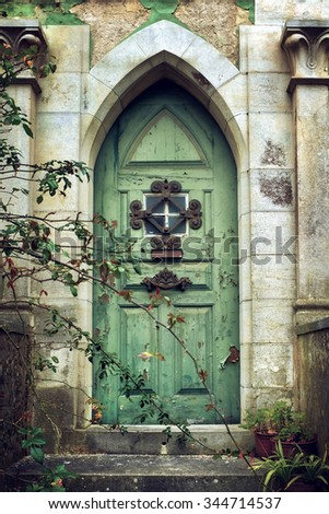 Old gothic door in romantic style with peeling green paint - stock photo