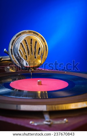 Old gramophone on blue background very close up - stock photo