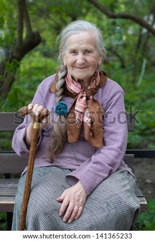 old grandmother with a long braid in the summer in the garden - stock photo
