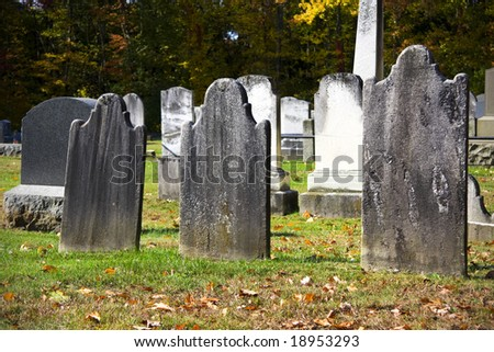 Old granite blank headstones in creepy churchyard during autumn season - stock photo