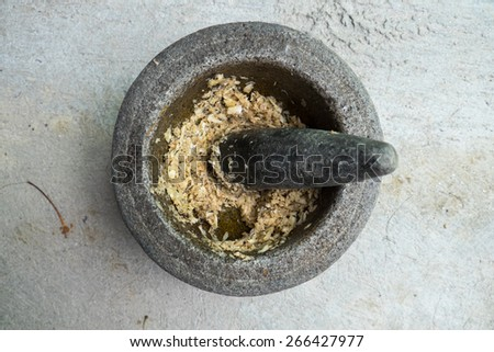 old granite mortar with pestle and garlic,Thailand - stock photo
