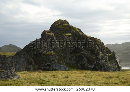 Old grass covered rock formation in the coast of Northern Norway. - stock photo