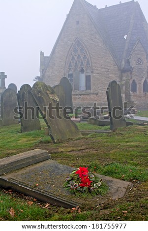 Old gravestones in cemetery with abandoned chapel - stock photo