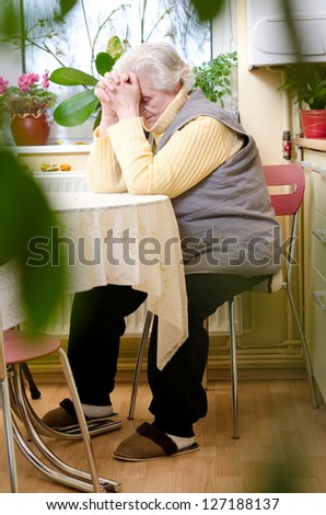 old gray-haired woman sitting in the kitchen - stock photo