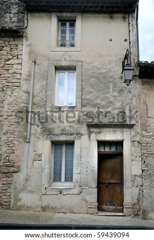 Old gray house facade with wooden door - stock photo