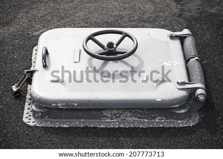 Old gray locked hatch on black ship deck - stock photo