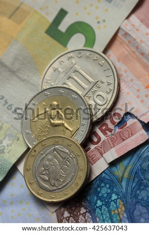 Old Greek and modern greek euro coins on Euro bank notes - stock photo