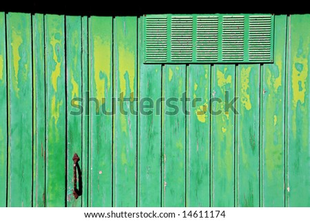 old green and yellow garage door, crusty and rusty - stock photo