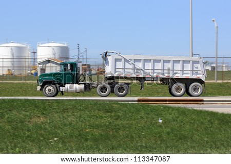 Old green dump truck on the road - stock photo