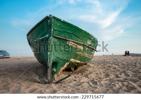 Old green fishing boat on the beach and blue sky up the horizon - stock photo