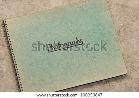 Old green photograph album with coil binding. - stock photo